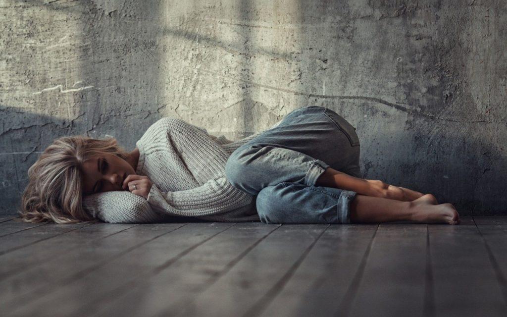 Грустная девушка блондинка лежит на полу из досок в джинсах и кофте