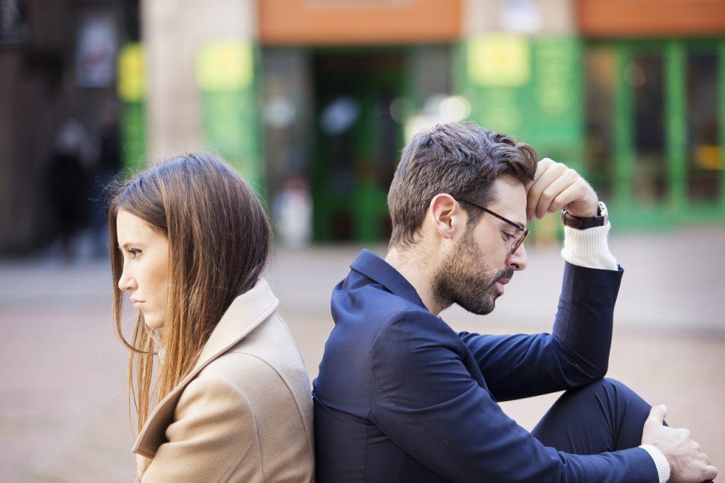 Мужчина и девушка сидят спиной к спине поругались проблемы в отношениях грустят пара