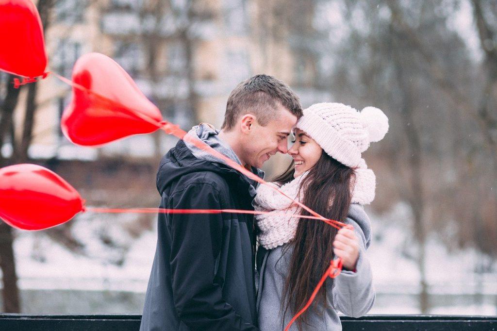 Счастливая пара, парень подарил девушке красные шарики в виде сердечек. Пара влюбленных зимой.