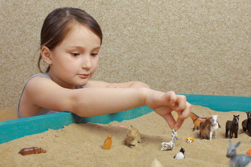Песочная терапия. Девочка ребенок играет в песке с животными.
