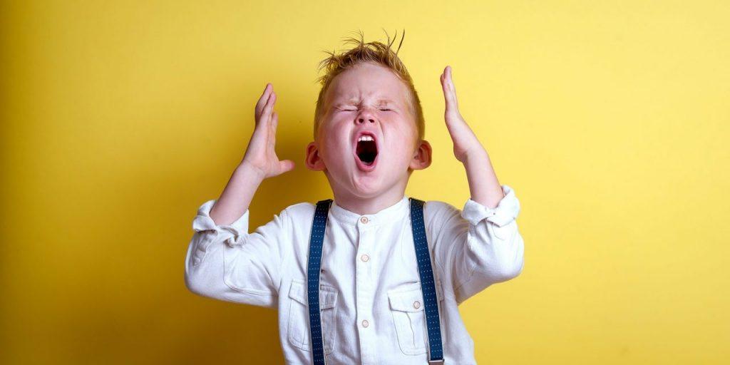 Ребенок кричит на желтом фоне в рубашке и подтяжках