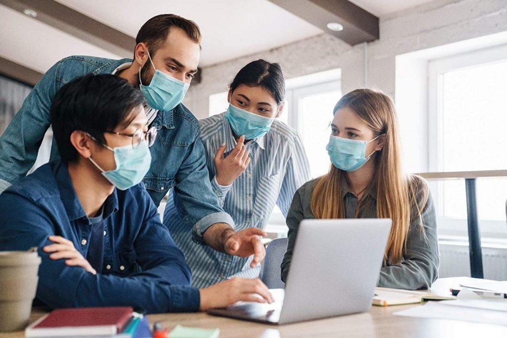 На работе общаются обсуждают в медицинских масках две девушки и два парня в очках перед ноутбуком