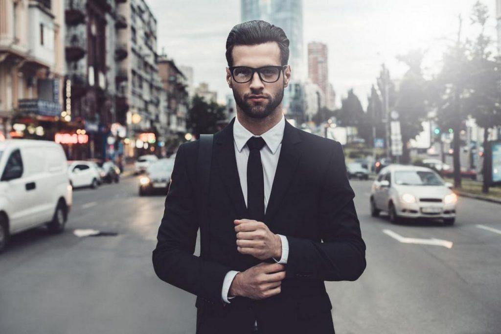 Уверенный в себе мужчина в деловом костюме и очках с модной прической застегивает запонку стоит на улице на фоне города и машин