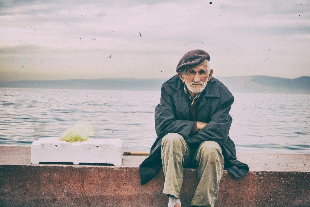 Пенсионер старик дедушка продает у моря сидит фото