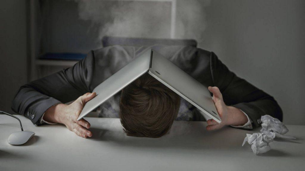 Уставший человек закрыл голову ноутбуком на работе