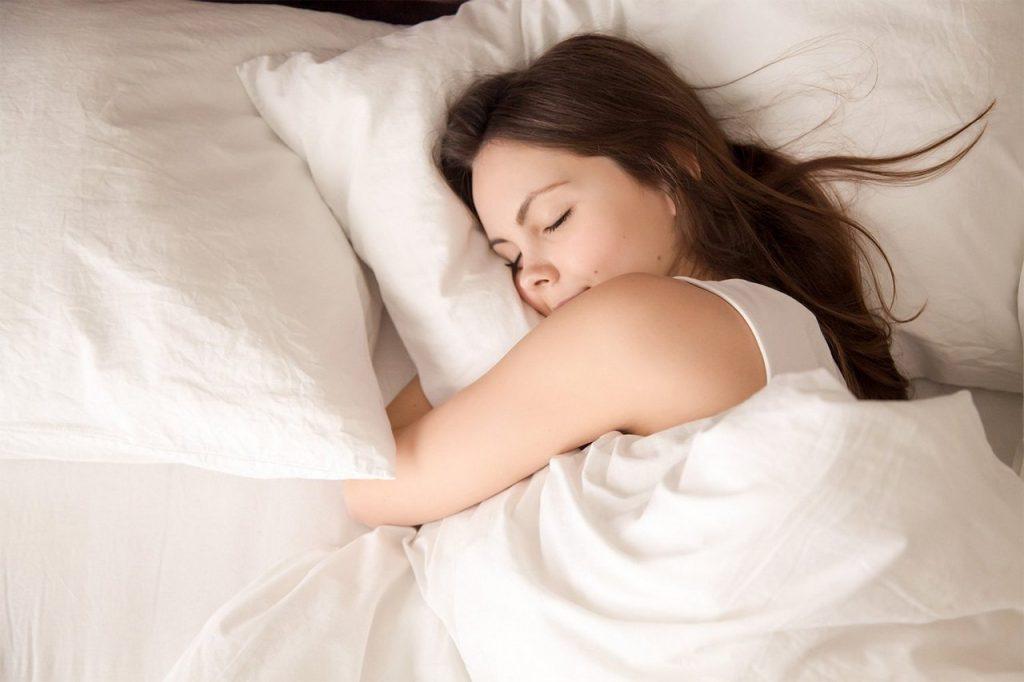 девушка спит на белом белье