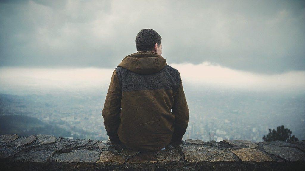 Одинокий человек один мужчина сидит на каменном заборе с видом на город в пасмурную погоду в куртке
