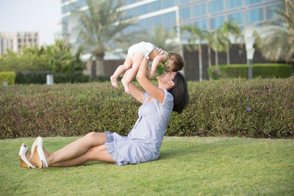 счастливая мама поднимает на руках меленького ребенка на зеленой траве