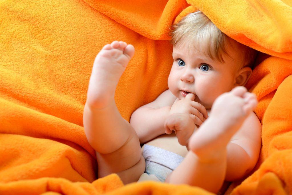 ребенок лежит в полотенце ногами вверх сосет палец