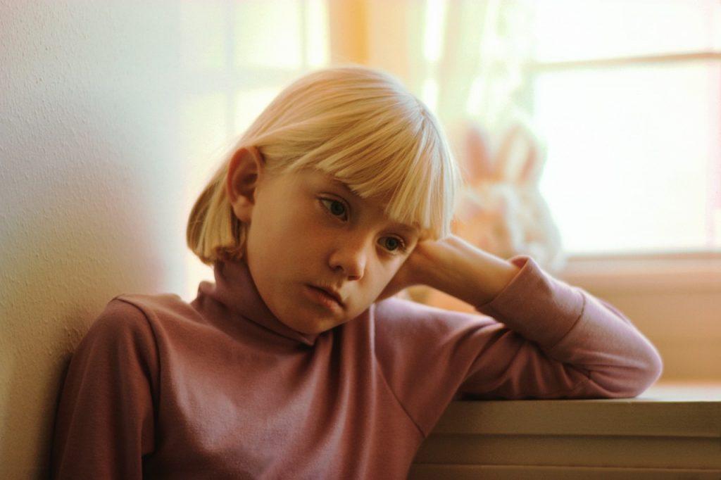 девочка блондинка с каре сидит возле стола опирается головой на руку