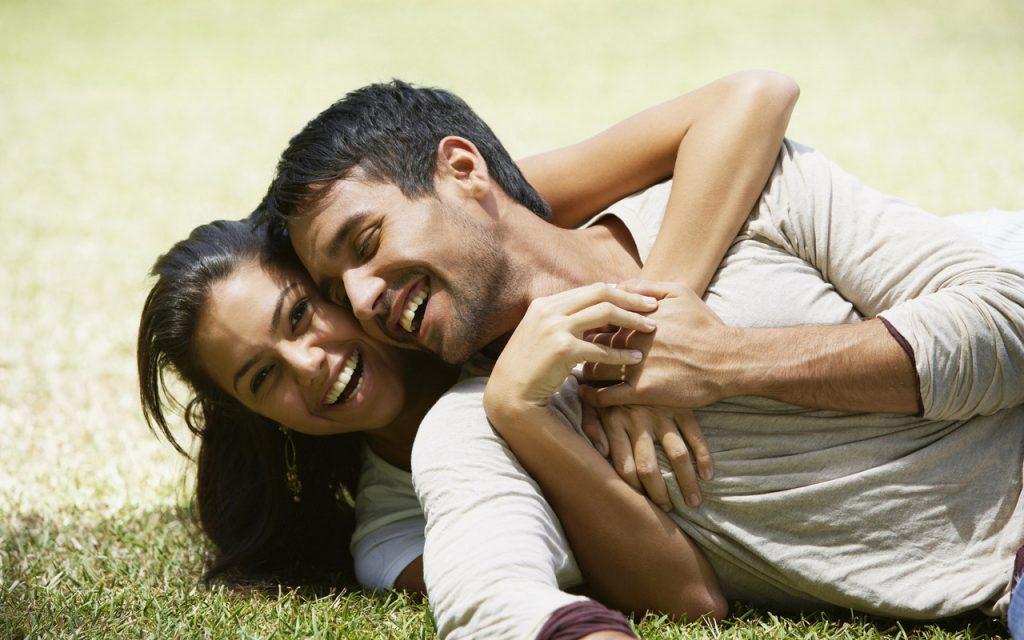 девушка и парень лежат и обнимаются на траве счастливые