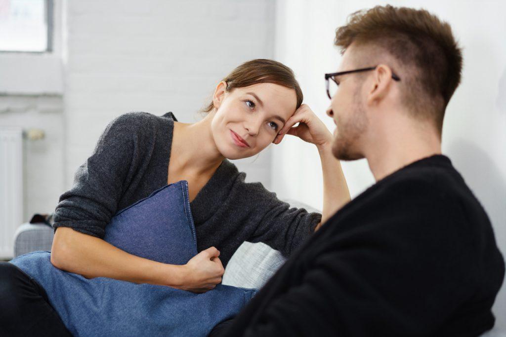 Жена женщина внимательно слушает мужа мужчину опираясь на руку с подушкой в руках