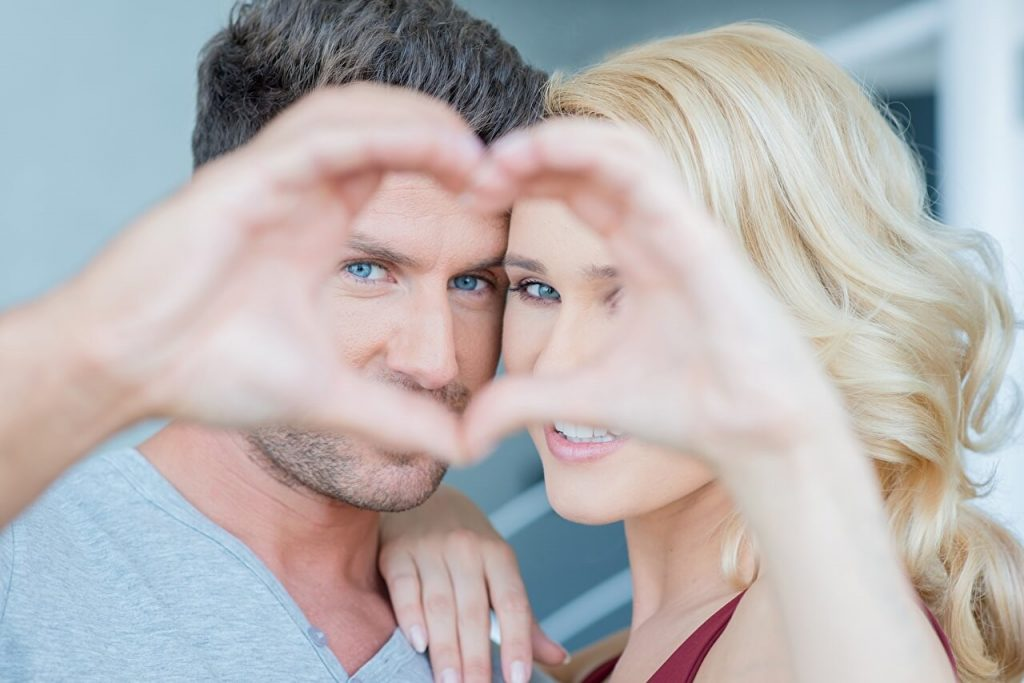 парень и девушка делают руками сердце