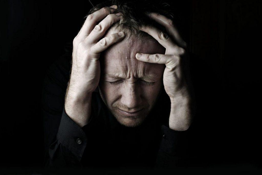 Мужчина обхватил и держит голову руками в черной рубашке на черном фоне