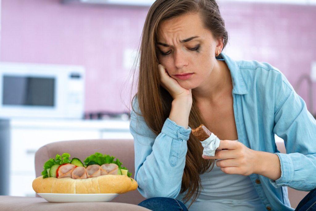 девушка с шоколадкой и большом количсетвом еды плачет и не может больше есть переедание лишний вес