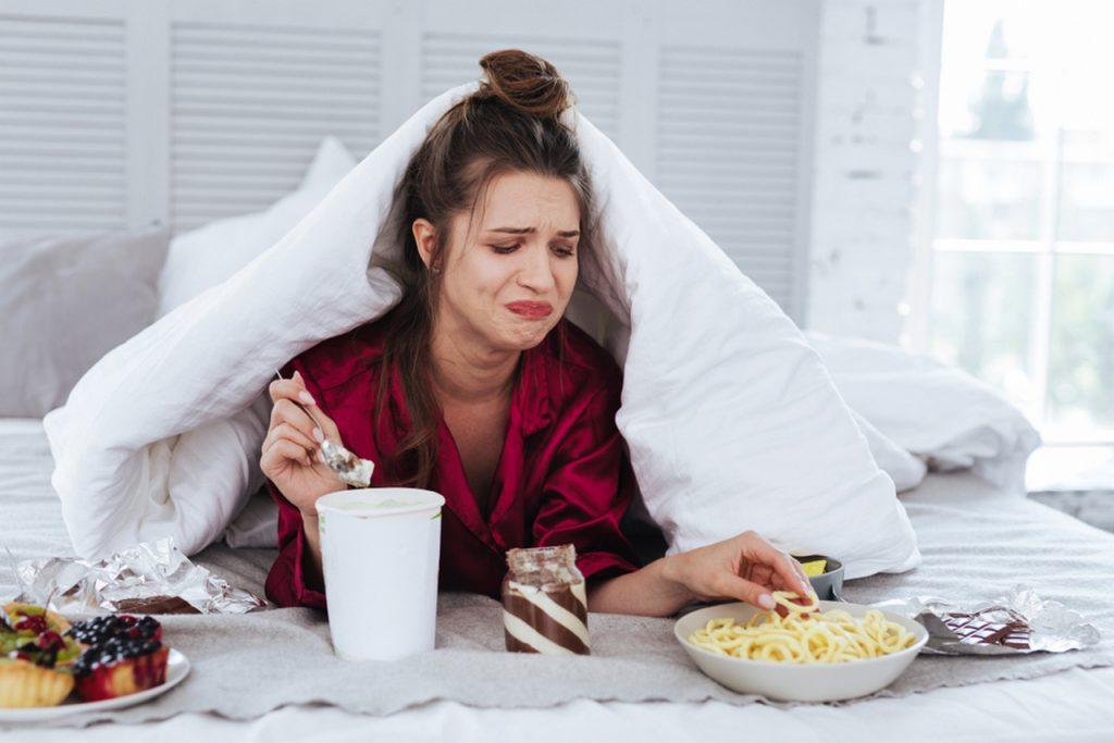 грустная женщина ест много сладкого в постели и плачет