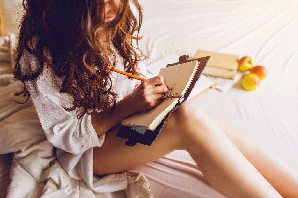 Девушка ведет пишет дневник карандашом в постели кровати сидя в рубашке ночнушке