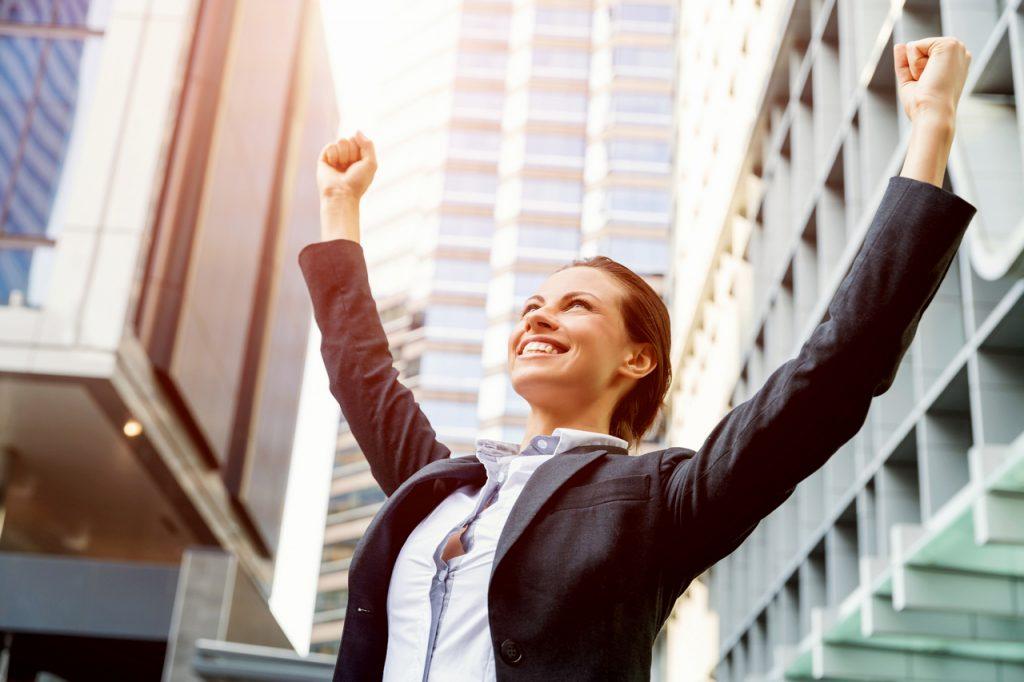 целеустремленная девушка женщина в деловом костюме пиджаке празднует радуется победе руки вверх