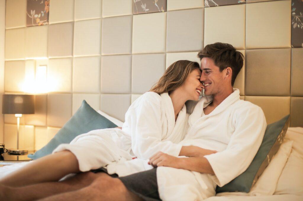парень с девушкой лежат на кровати в гостинице в белых халатах