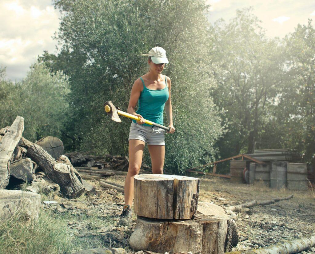 девушка с топором рубит дрова