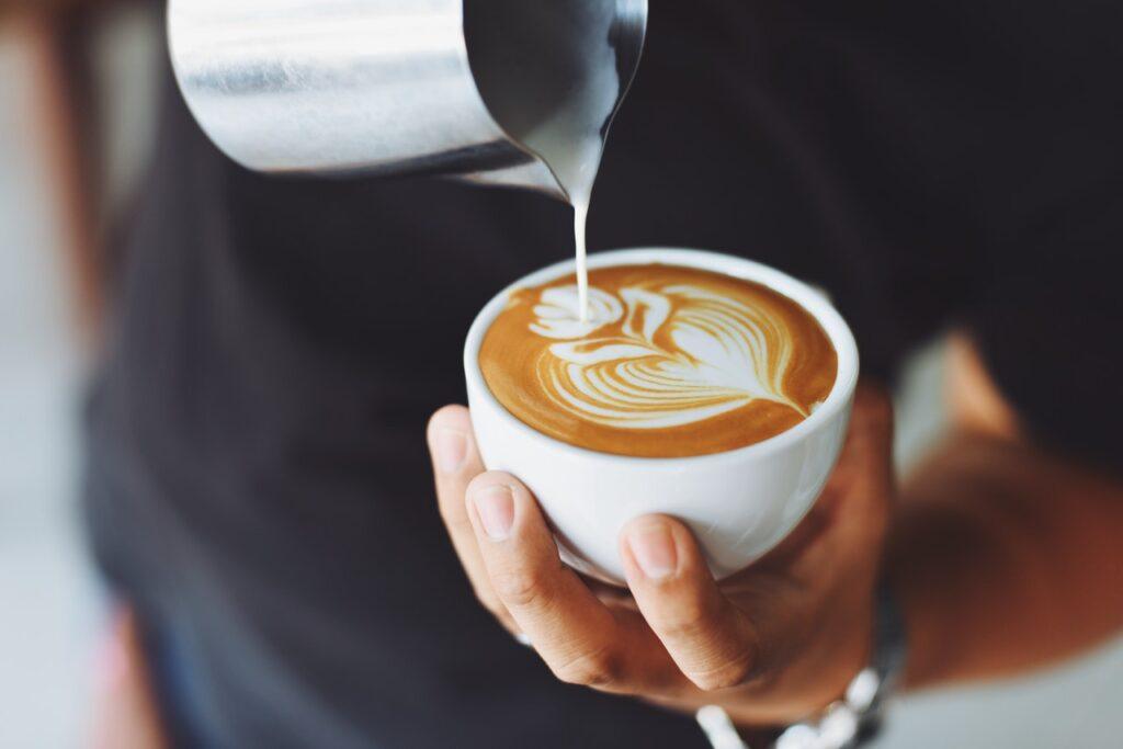 кофе с рисунком цветка из молока в руке у мужчрны
