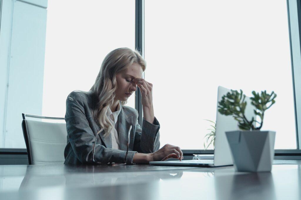 девушка блондинка в офисе грустит и страдает от стресса перед ноутбуком